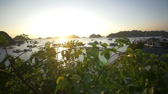 Bay filled with traditional boats and islands at sunset Stock Footage