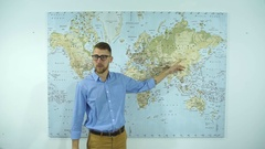 Young businessman with glasses shows of the country on the world map Stock Footage