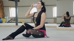 Dancing instructor has a rest on the floor afer a fitness class Stock Footage