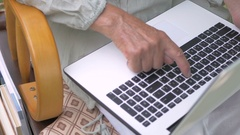 Granny is typing on a laptop keyboard. Stock Footage