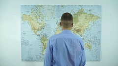 A businessman looks at a map of the world Stock Footage