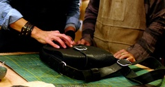 Craftswomen having discussion on leather bag Stock Footage