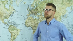 A young bearded man in glasses looks at the world map and making plans Stock Footage