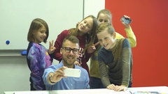 A young bearded man makes a selfie with a group of his schoolkids Stock Footage