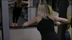 Blonde girl training at the gym. Woman engaged in fitness Stock Footage