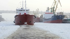 Oil tanker moving through the ice on frozen river, along the harbor with cranes, Stock Footage