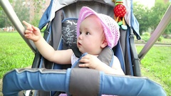A cute little girl is surprised. The child is sitting in a baby carriage. Stock Footage