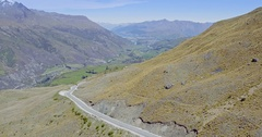 Aerial shot of car driving over mountain range to queenstown, New Zealand Stock Footage