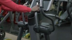 Blonde girl training at the gym on the elliptical Stock Footage