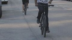 Two cyclist pedal down urban street Stock Footage