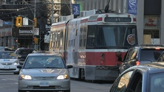 Toronto streetcar travelling along Queen Street at rush hour Stock Footage