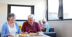 Senior couple interacting with eachother while having breakfast Stock Footage