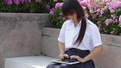 Portrait of thai high school student uniform beautiful girl using her tablet Stock Footage