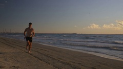 Runner doing workout on the beach resting and running again Stock Footage