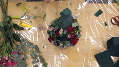 Female hands florist make a bouquet of roses, pine needles, leaves Stock Footage