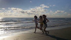 Three gorgeous women running on the beach during workout Stock Footage