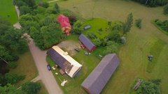 Aerial shot of the cabin houses with roofers installing shingles in I.. Stock Footage