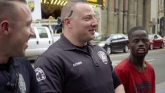Police officer having fun telling joke to Welven Da Great laughing Hollywood LA Stock Footage