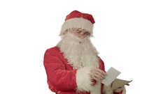 Santa Claus reading letters from children on white background Stock Footage