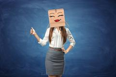 Young beautiful woman showing her thumb up and wearing cardboard box with drawn Stock Photos