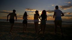 Group of five friends running together towards the sea on a beach at sunset.. Stock Footage