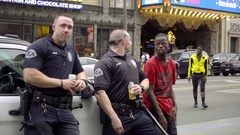 Police officers leaning on car with Welven Da Great on Hollywood Blvd LA Stock Footage