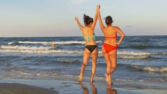 Females playing on the beach in the water and dancing Stock Footage