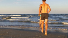 Romantic couple playing and teasing one another in the sea Stock Footage