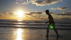 Male running on wet sandy beach during workout in slow motion Stock Footage