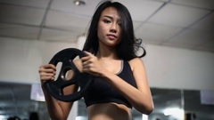 Asian woman exercise with dumbbells in gym Stock Footage