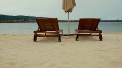 Two empty sun loungers and parasols on the sandy beach. Stock Footage