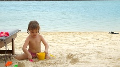Portrait of a child playing in the sand on a tropical beach. Stock Footage