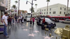 Panning on Hollywood Boulevard Walk of Fame with gold chairs and stars LA CA Stock Footage