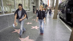 People walking on Walk of Fame stars on Hollywood Boulevard tourists Los Angeles Stock Footage