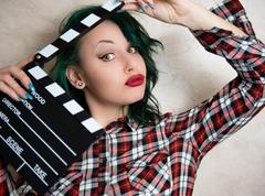 Young alternative girl face with movie clapper Stock Photos