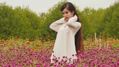 Vietnamese girl with long black hair standing in a plantation purple flowers Stock Footage