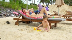 Young beautiful mother lying on a deck chair and looking after a child. Stock Footage
