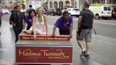 Madame Tussaud wax figure Marilyn Monroe statue rolling in street by workers LA Stock Footage