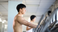 Asian man exercise on elliptical trainer machine Stock Footage