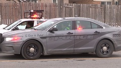 Police officers at scene of pedestrian stuck and killed by car on city street Stock Footage