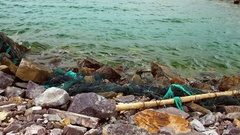 Fishing net and gear thrown by waves on the shore. Stock Footage