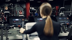 Exercise bike - Young woman exercising on a stationary bike in a gym Stock Footage