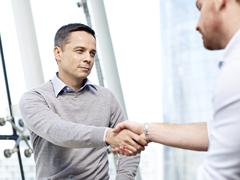 Businessman shaking hands with competitor Stock Photos