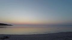 Sunrise on the clear sky in the calm sea. Light cirrus clouds, sandy beach Stock Footage