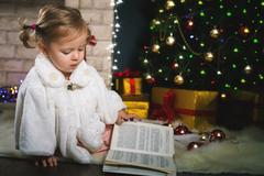 Baby girl reading book with fairy tale at Christmas Kuvituskuvat