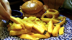 Hand dipping fries into ketchup alongside a burger and fries. Stock Footage