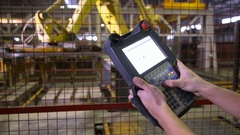 Man operating robotic equipment with remote control at industrial factory, plant Stock Footage