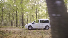 White minivan car driving slow through forest on gravel road side shot 4K Stock Footage