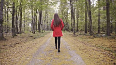 Tracking brown long hair woman in red jacket on high heels in forest 4K Stock Footage