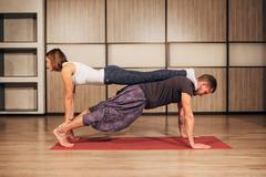 Young man and woman doing yoga in pair Stock Photos